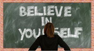 """kid in front of chalk board that says, """"Believe in yourself""""."""
