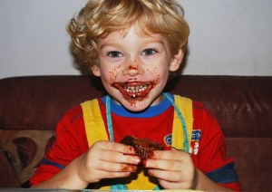 young boy eating a cupcake with chocolate on his mouth