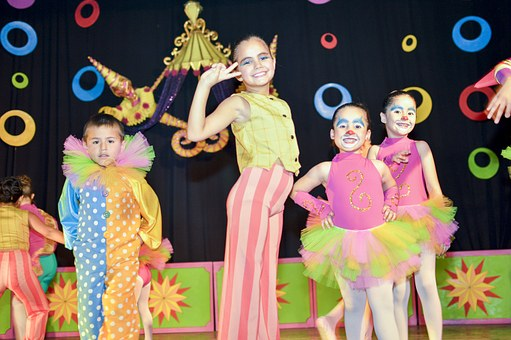 kids dressed in clown suits on a stage