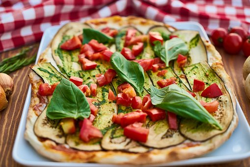 healthy pizza with sliced tomatoes and spinach
