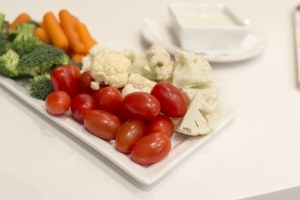 platter of tomatoes cauliflower carrots and ranch dressing
