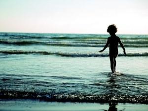 Little kid walking on the beach