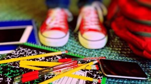 Sneakers standing in pile of notebooks and pencils