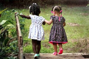 two little girls walking and holding hands