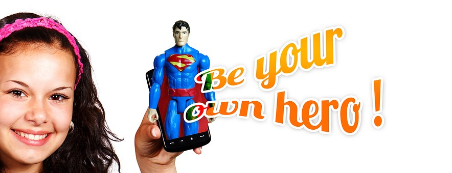 "Girl holding a Superman doll that says ""Be Your Own Hero"""