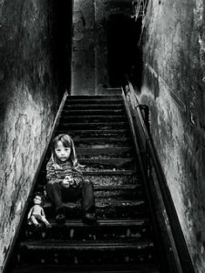 girl sitting in dark staircase with a doll
